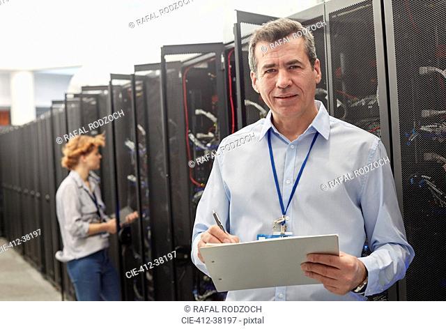 Portrait confident male IT technician with clipboard in server room