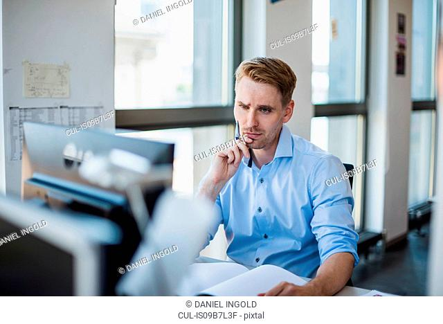 Mid adult businessman at desk with paperwork looking at desktop computer