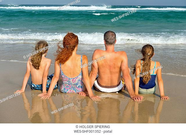 Australia, New South Wales, Pottsville, family sitting at the ocean