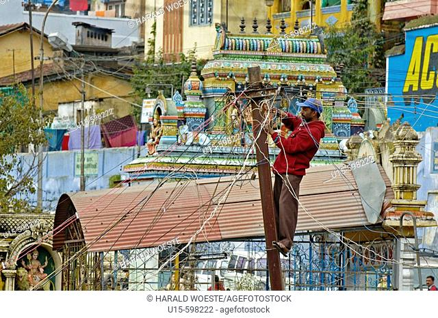 India. Tamil Nadu. Coonoor. Indian electrician working on wiring post in Coonoor