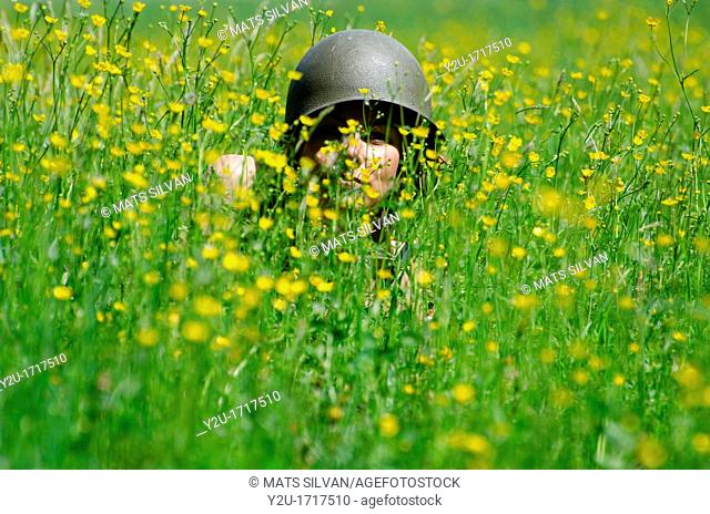 Woman with military helmet in the field with yellow flowers