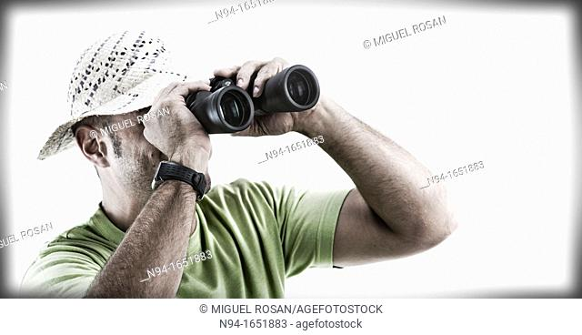 Closeup of man with hat looking through binoculars