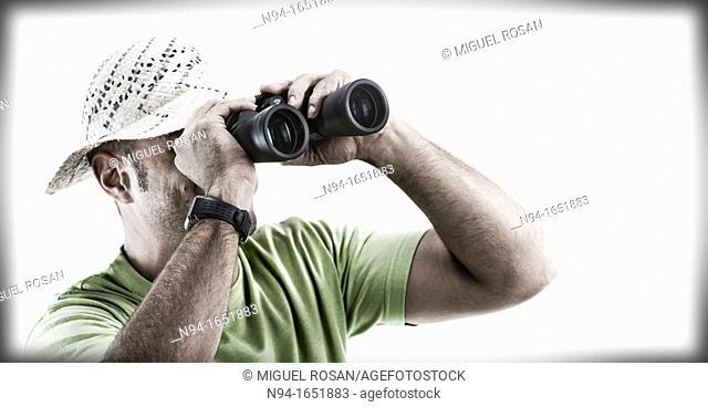 Closeup of man with hat looking through binoculars