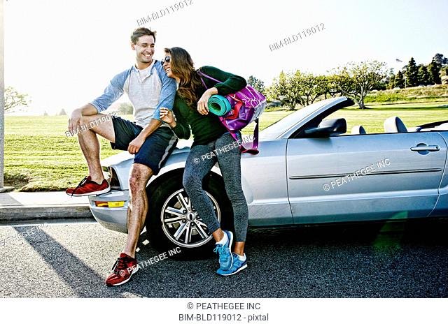 Couple wearing workout gear by convertible