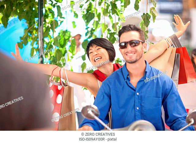 Happy young couple with shopping bags riding on moped in city