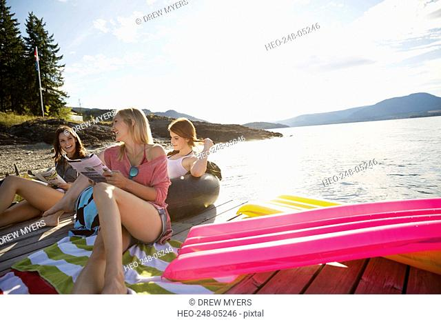 Young women relaxing hanging out sunny lake dock
