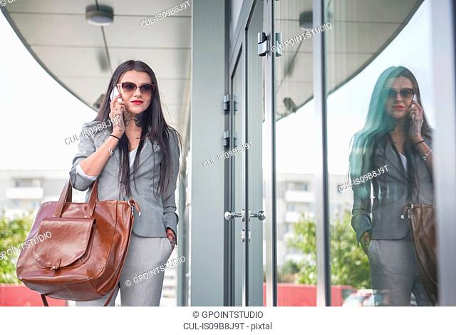 Businesswoman walking beside office building, using smartphone