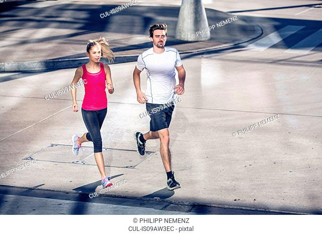 High angle view of couple wearing sports clothing jogging in urban area