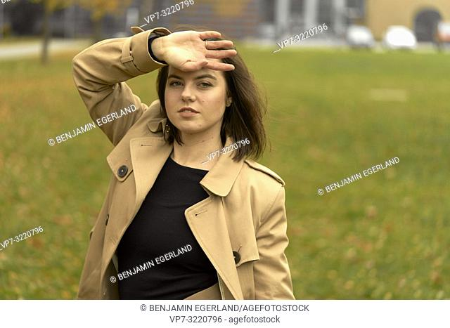 portrait of young woman outdoors in park during autumn, wearing coat, in Munich, Bavaria, Germany