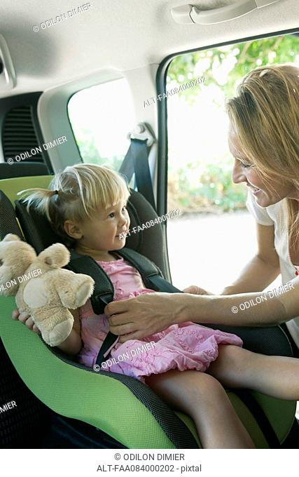 Woman fastening little girl into car seat