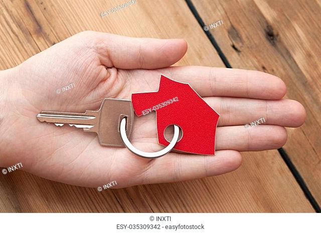 Human hand holding house key on a wood background