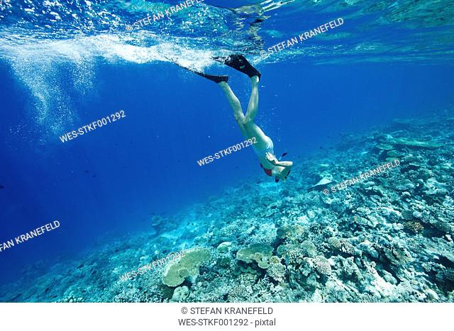 Maldives, woman snorkeling in the Indian Ocean