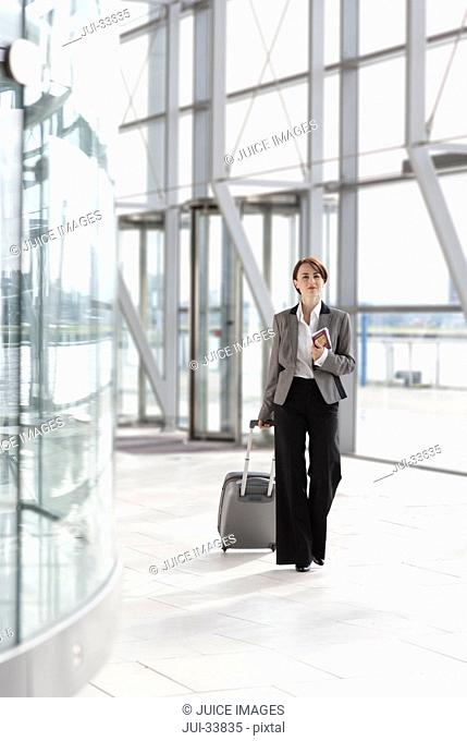 Businesswoman with passport pulling suitcase in airport