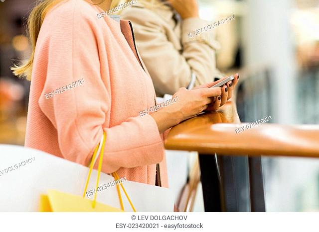 sale, consumerism, technology and people concept - close up of young women with smartphones and shopping bags in mall