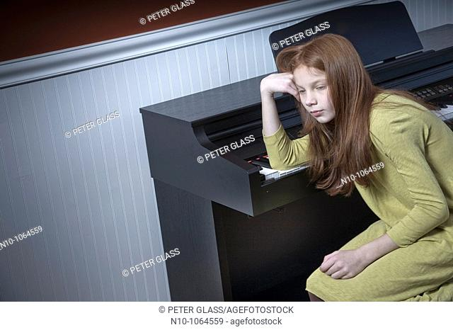 Preteen redhead girl sitting at an electric piano