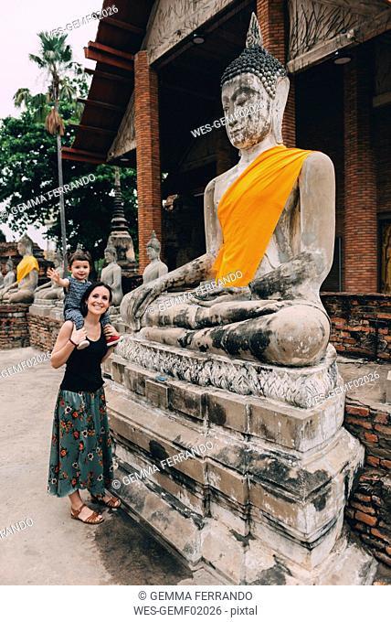 Thailand, Ayutthaya, mother and little daughter standing besides Buddha statue at Wat Yai Chaya Mongkhon