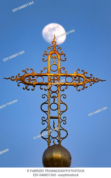 Cross in front of a waxing gibbous moon