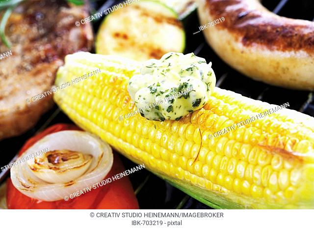 Barbecue scene, corncob with a dollop of herb butter in the foreground