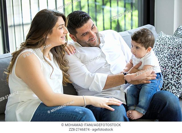 Father and mother with their baby boy sitting indoors smiling