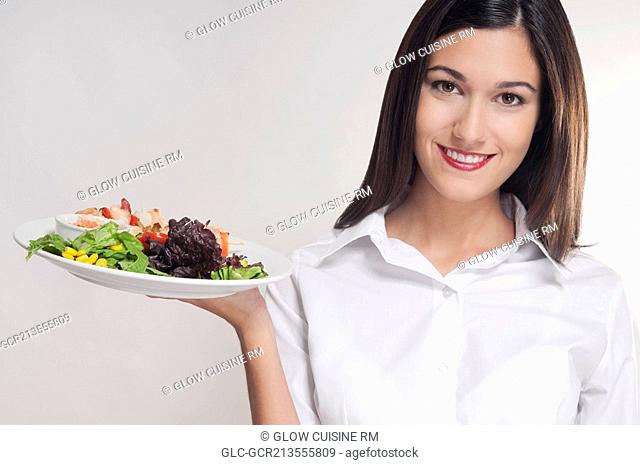 Portrait of a young woman holding a platter of shish kebabs