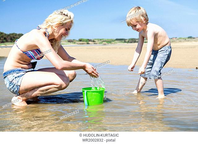 Mother and son on beach playing with water bucket
