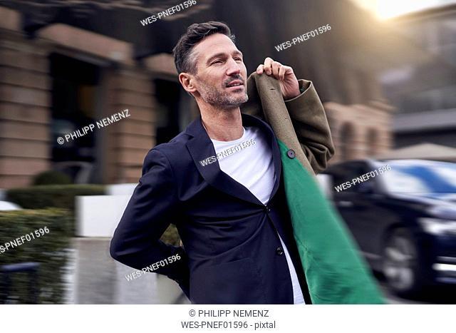 Mature man dressing his coat