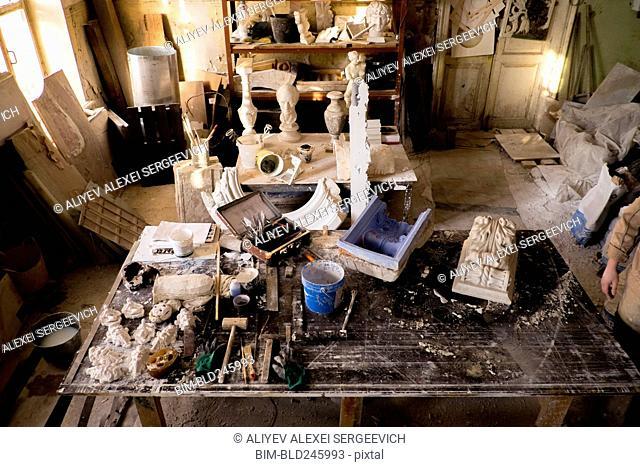 Caucasian artist in messy studio