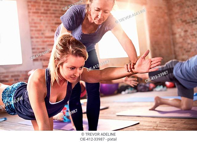 Fitness instructor helping young woman practicing bird dog plank in exercise class gym studio