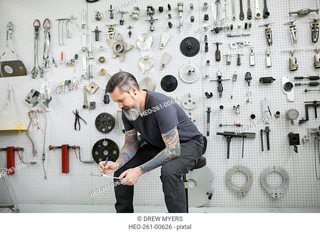 Helicopter mechanic with clipboard near tools on wall