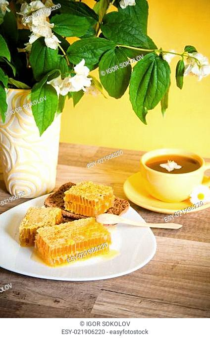 Honeycomb with a cup of tea and a bouquet of blooming Jasmine