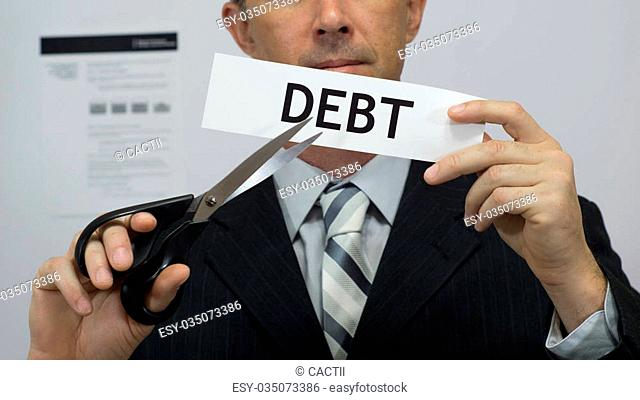 Male office worker or businessman in a suit and tie cuts a piece of paper with the word debts on it as a debt reduction business concept