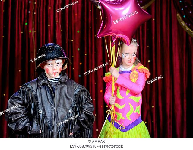 Portrait of Young Male Clown Wearing Leather Jack and Helmet Standing with Young Female Clown Wearing Brightly Colored Costume and Holding Balloons on Stage...