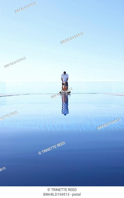 Couple relaxing near infinity pool overlooking scenic view