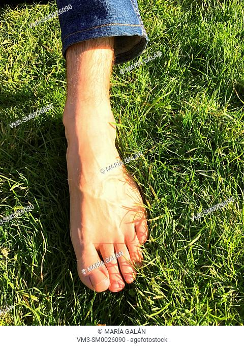 Man's foot on the grass
