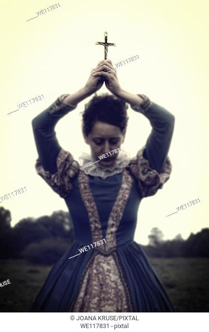 a lady in a renaissance dress holding a crucifix