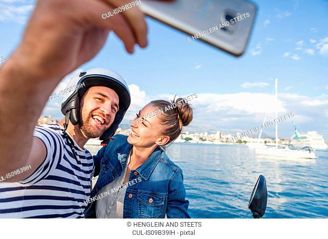 Young moped couple taking selfie on harbour, Split, Dalmatia, Croatia