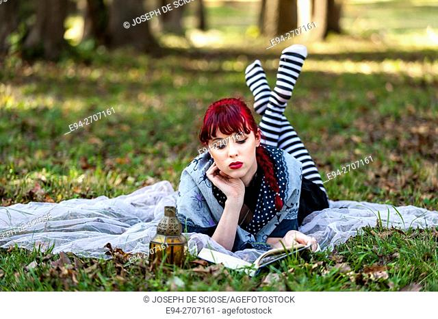 A pretty 23 year old red headed woman outdoors, lying on the grass looking down at a book