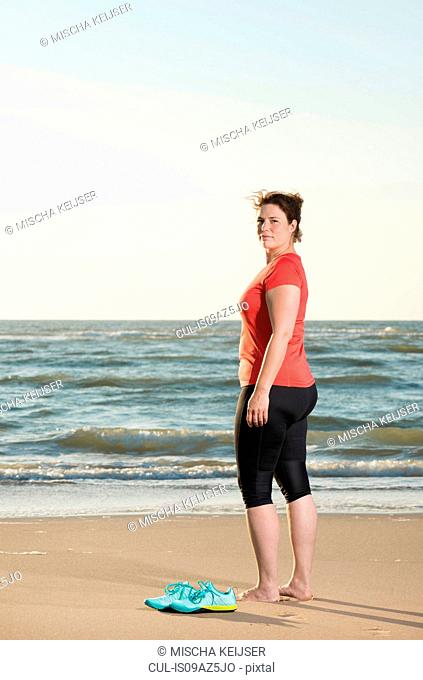 Mature woman standing on beach at sunset, portrait