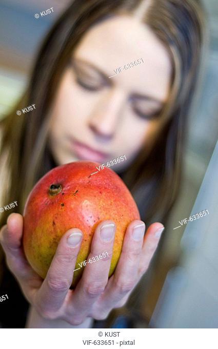 junge Frau riecht genuesslich an suesser Mango - Nieder÷sterreich, Ísterreich, 14/02/2008