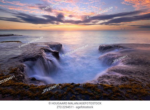 Landscape phot of a sunrise sky over seaside rocks. Arniston/Waenhuiskrans, Western Cape, South Africa