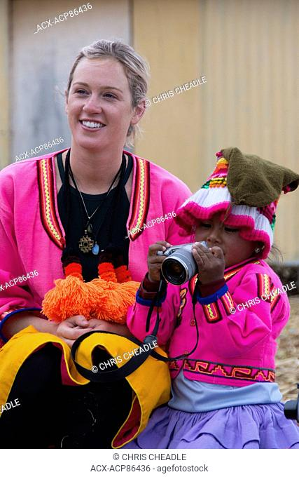 Traveller interacts with local child of floating reed islands of Uros, Lake Titicaca, Peru