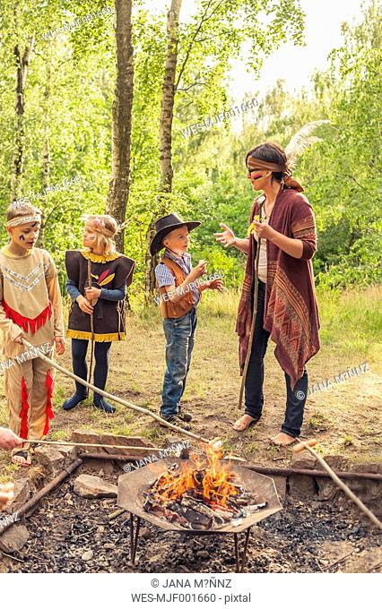 Germany, Saxony, Indians and cowboy party, Children rasting marshmallows on sticks
