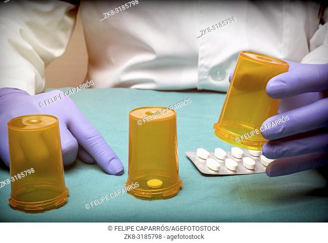 Doctor plays to Thimblerig with bottles of medicine, conceptual image