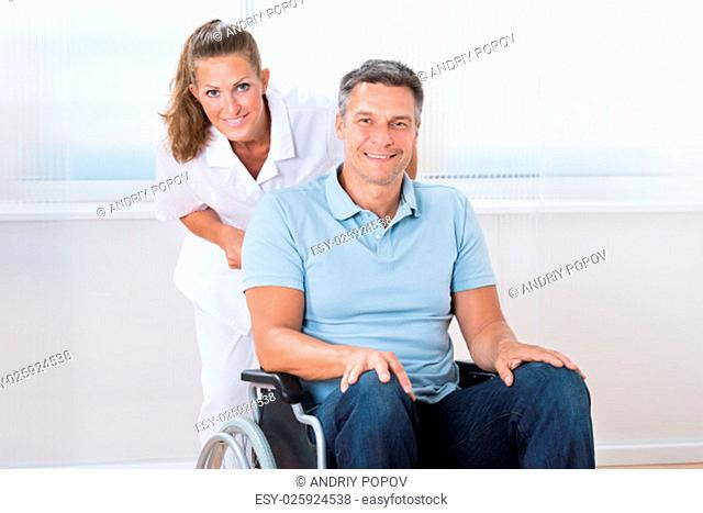 Happy Female Doctor Carrying Male Patient On Wheelchair