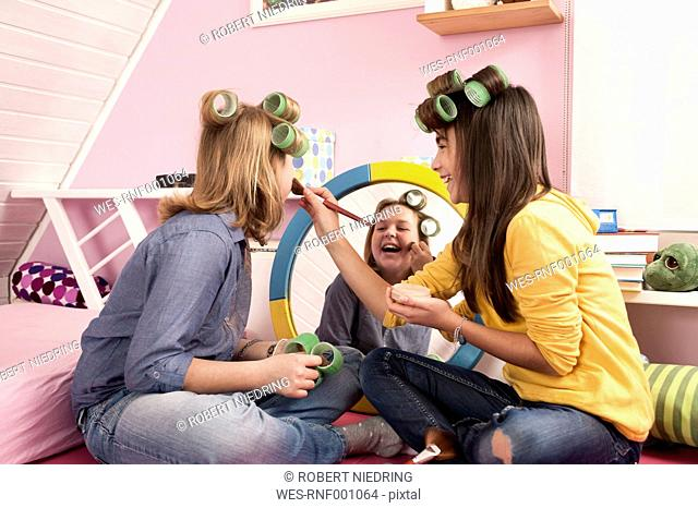Girls with hair rollers applying make up, smiling