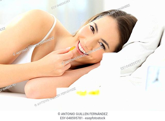 Front view portrait of a happy woman taking supplement pill in the bed in the morning