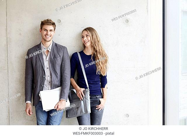 Smiling young couple at concrete wall