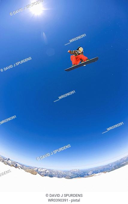 A Snowboarder flying high above the mountains and glaciers in the sun