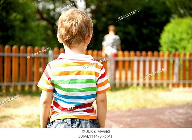 Young boy standing in playground, rear view