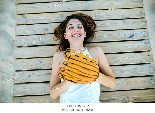 Young woman lying on wooden path laughing with baseball glove